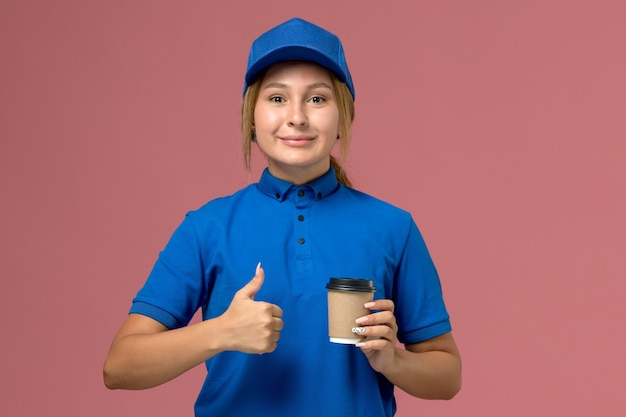 Giovane corriere femminile di vista frontale in uniforme blu che posa e che tiene la tazza di caffè di consegna sulla parete rosa, donna di consegna uniforme di servizio