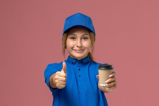 Giovane corriere femminile di vista frontale in uniforme blu che posa e che tiene la tazza di caffè di consegna che sorride sulla parete rosa, donna di consegna dell'uniforme di lavoro di servizio