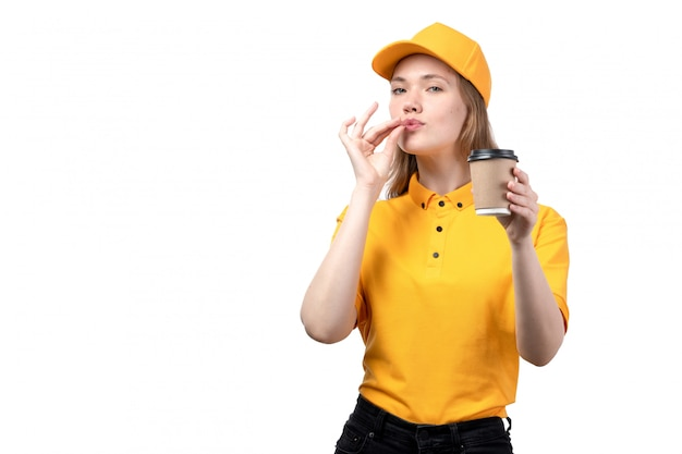 A front view young female courier female worker of food delivery service holding coffee cup and showign tasty sign on white