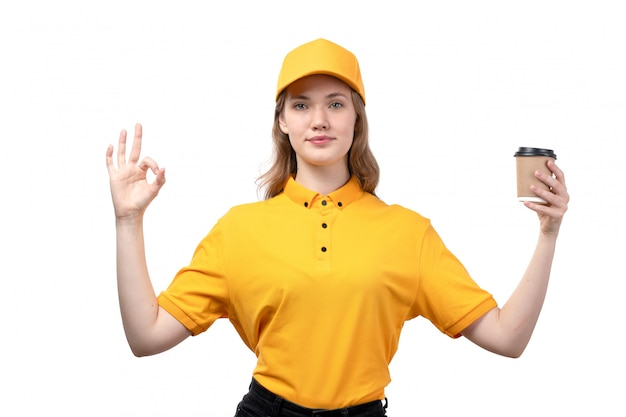 A front view young female courier female worker of food delivery service holding coffee cup smiling on white