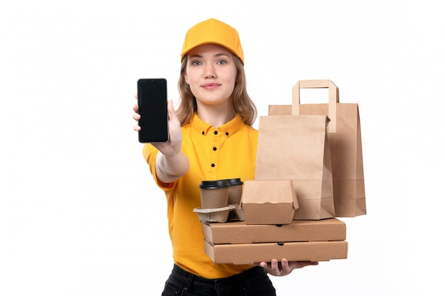 A front view young female courier female worker of food delivery service holding coffee cups food packages while showing a phone on white