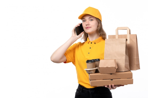 A front view young female courier female worker of food delivery service holding coffee cups food packages while talking on phone on white