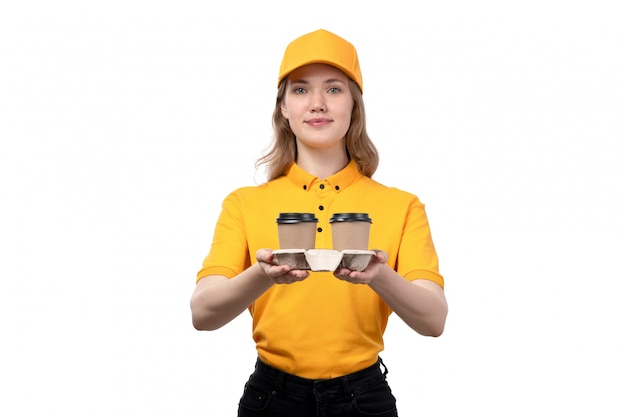 A front view young female courier female worker of food delivery service holding coffee cups and smiling on white