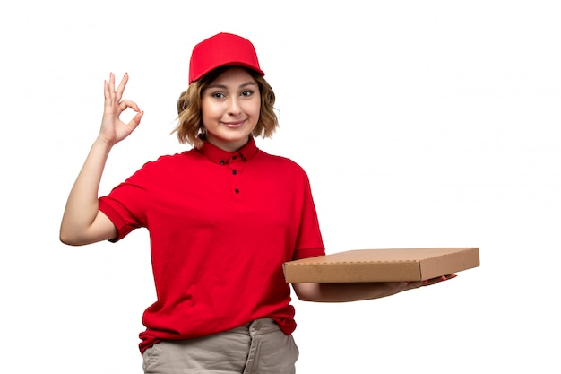 A front view young female courier female worker of food delivery service holding food delivery package smiling on white