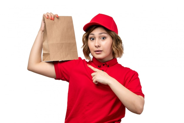A front view young female courier female worker of food delivery service holding food delivery package on white