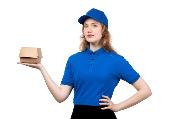A front view young female courier female worker of food delivery service holding food package on white
