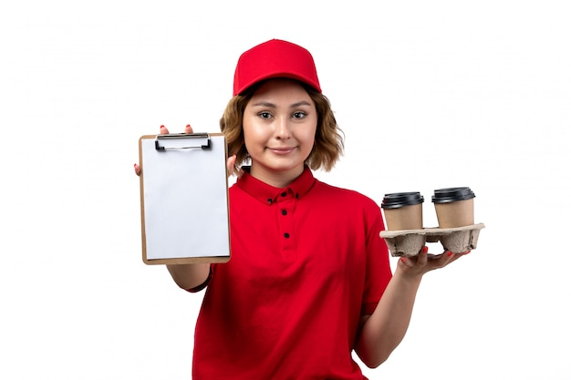 A front view young female courier female worker of food delivery service holding notepad and coffee cups on white