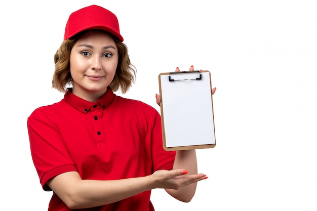A front view young female courier female worker of food delivery service holding notepad for signatures and smiling on white