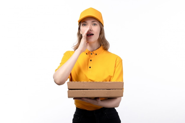 A front view young female courier female worker of food delivery service holding pizza boxes and whispering on white