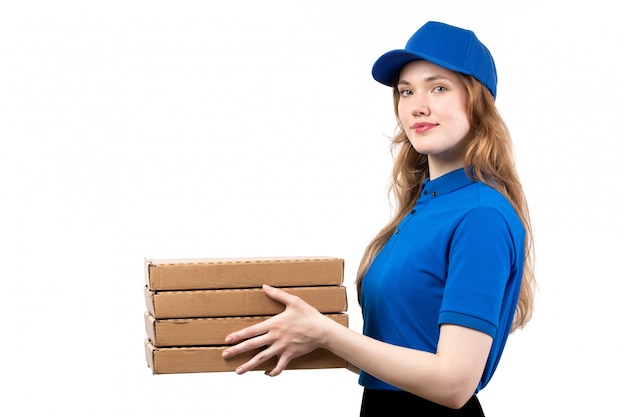 Una giovane lavoratrice femminile del corriere femminile di vista frontale delle scatole di consegna della pizza della tenuta di servizio di distribuzione dell'alimento su bianco