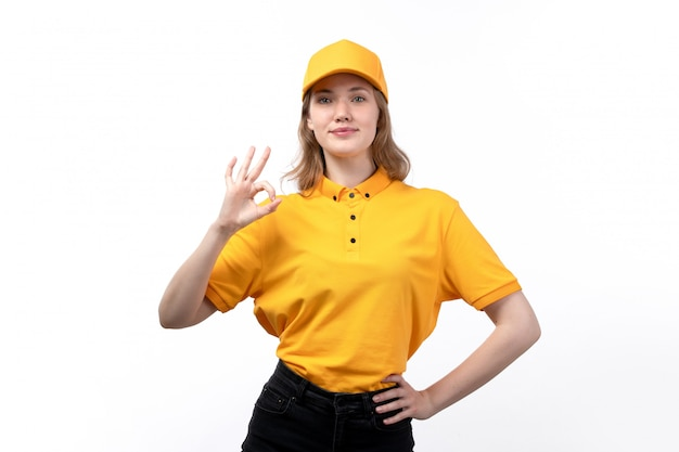 A front view young female courier female worker of food delivery service posing with alright sign smiling on white
