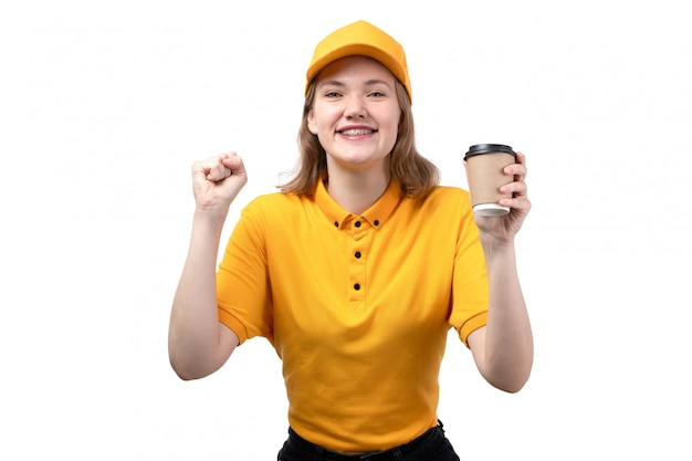 A front view young female courier female worker of food delivery service smiling and enjoying holding cup with coffee on white