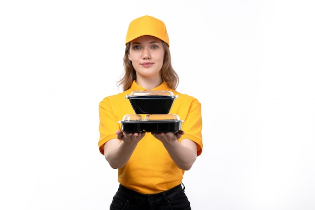A front view young female courier female worker of food delivery service smiling holding bowls with food on white
