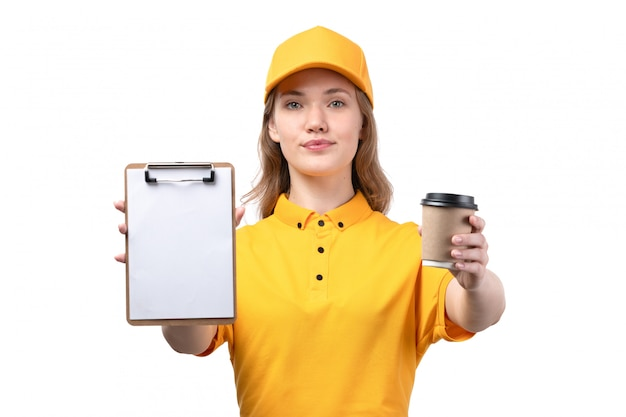 A front view young female courier female worker of food delivery service smiling holding cup with coffee and notepad for signature on white