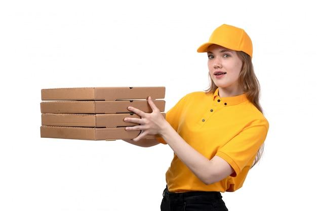 Una giovane lavoratrice femminile del corriere femminile di vista frontale delle scatole sorridenti di consegna dell'alimento della tenuta di servizio di distribuzione di alimenti su bianco