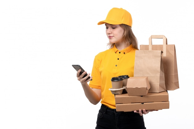 A front view young female courier female worker of food delivery service smiling holding food packages and coffee cups and using a phone on white