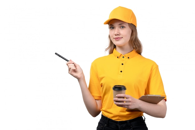 A front view young female courier female worker of food delivery service smiling holding pen and coffe cup on white