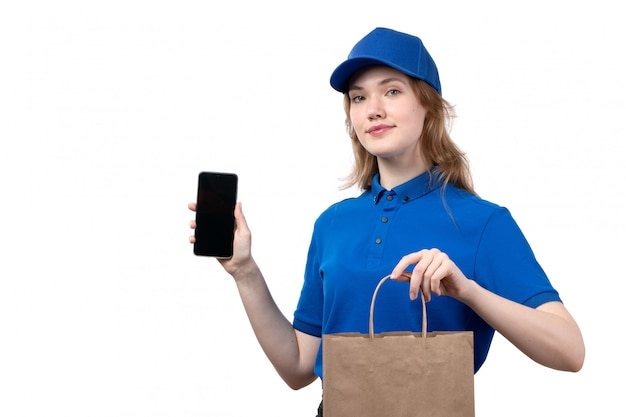 A front view young female courier female worker of food delivery service smiling holding smartphone and package with food on white