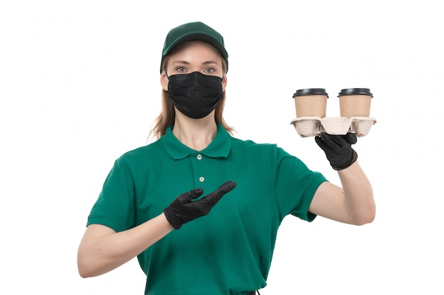 A front view young female courier in green uniform black gloves and black mask holding coffee cups