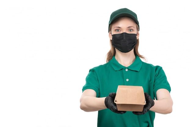 Un giovane corriere femminile di vista frontale in guanti neri uniformi verdi e maschera nera che tiene consegna del pacchetto di consegna dell'alimento