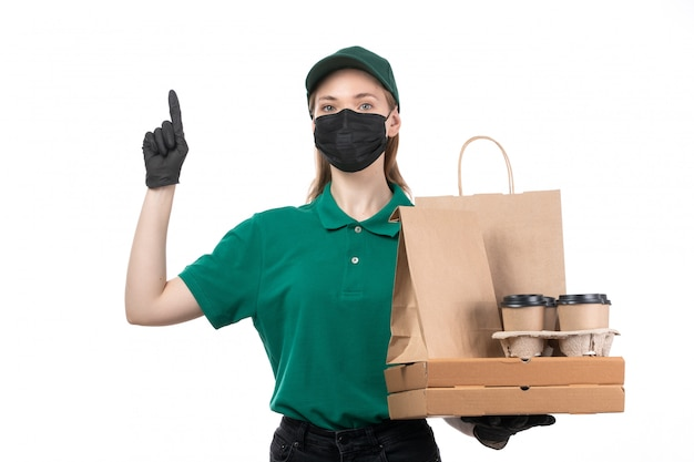 A front view young female courier in green uniform black gloves and black mask holding food delivery packages delivering