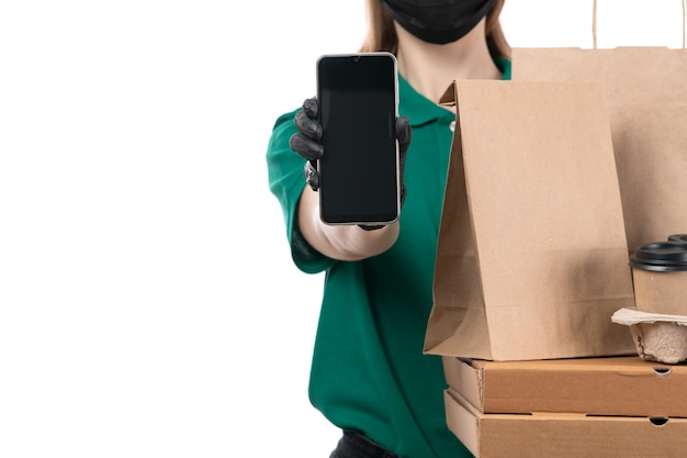A front view young female courier in green uniform black gloves and black mask holding food delivery packages and phone delivering