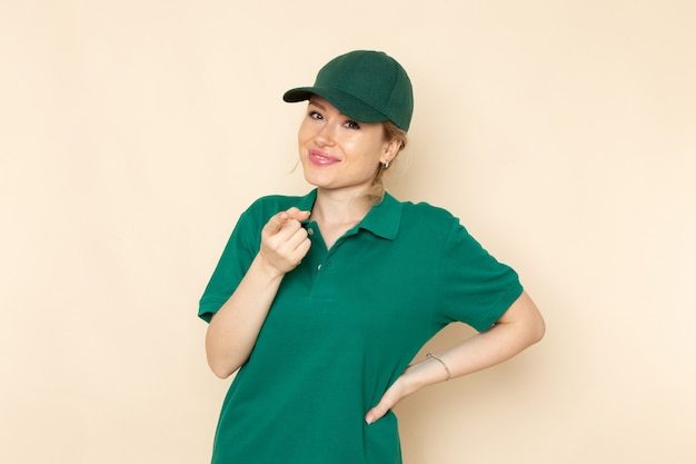 Front view young female courier in green uniform and green cape posing and smiling on the light space   woman work uniform