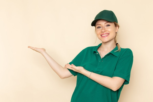 Front view young female courier in green uniform and green cape posing with smile on the light space   woman work uniform