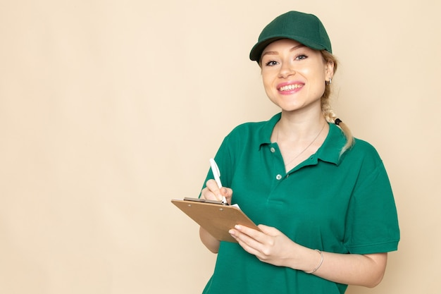 Front view young female courier in green uniform and green cape writing down notes smiling on the light space   woman uniform