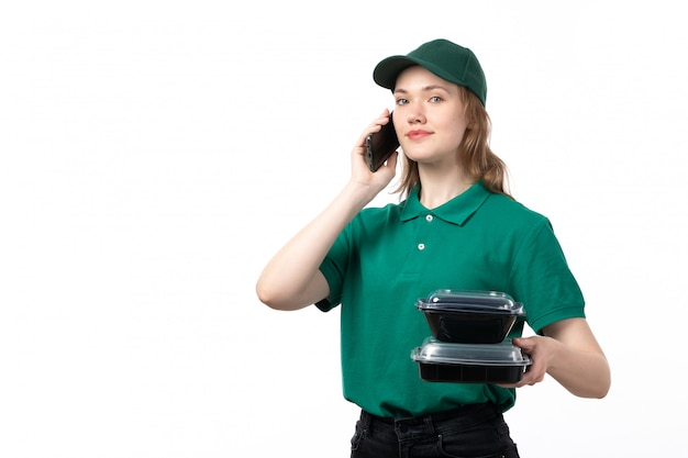 A front view young female courier in green uniform holding bowls with food and talking on phone smiling on white