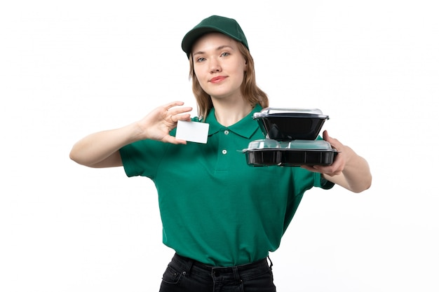 A front view young female courier in green uniform holding bowls with food and white card smiling on white