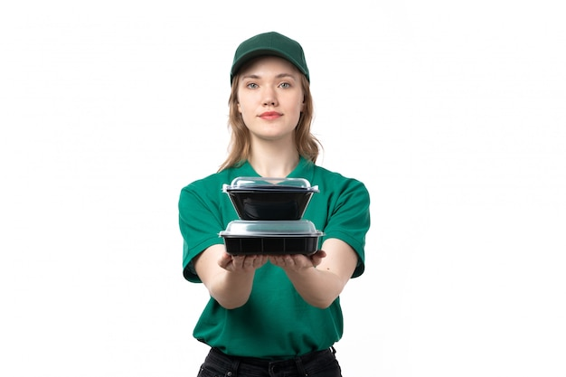 A front view young female courier in green uniform holding bowls with food on white