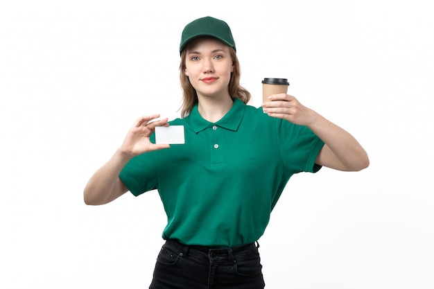 A front view young female courier in green uniform holding coffee cup and white card on white