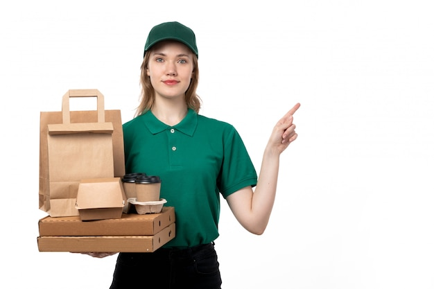 A front view young female courier in green uniform holding coffee cups and food delivery packages on white