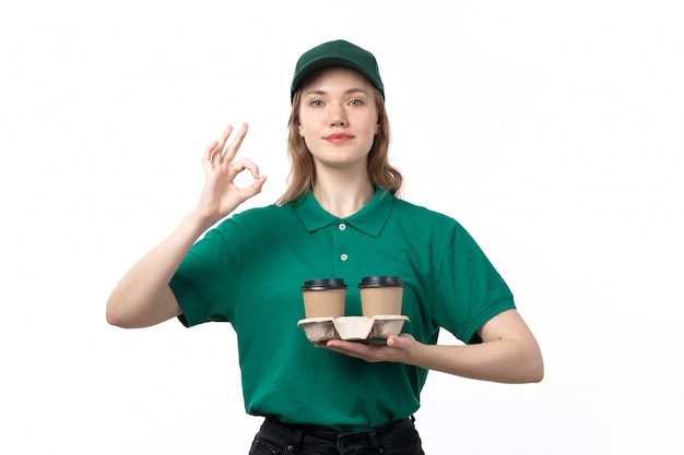 A front view young female courier in green uniform holding coffee cups and showing alright sign on white