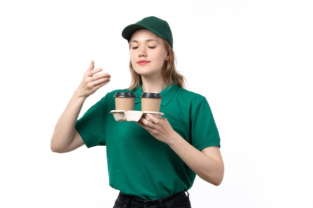 A front view young female courier in green uniform holding coffee cups smelling their scent