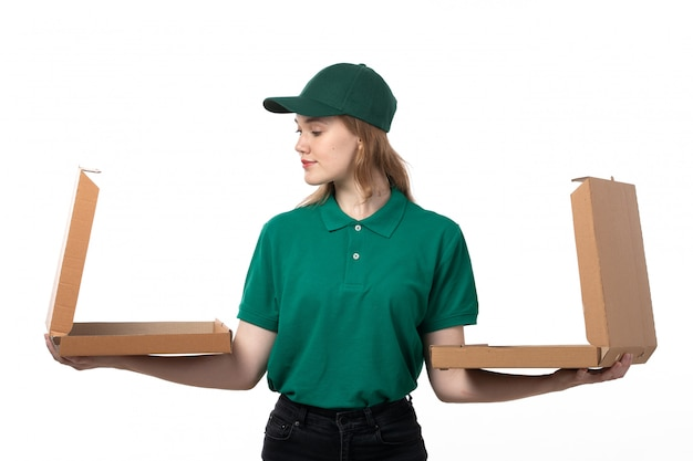 A front view young female courier in green uniform holding empty boxes of pizza and smiling