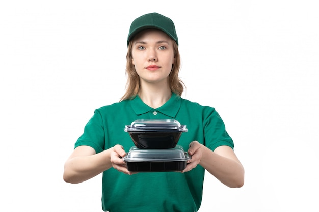 A front view young female courier in green uniform holding food bowls