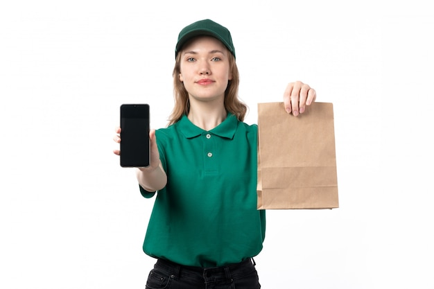 A front view young female courier in green uniform holding package with food and smartphone showing them