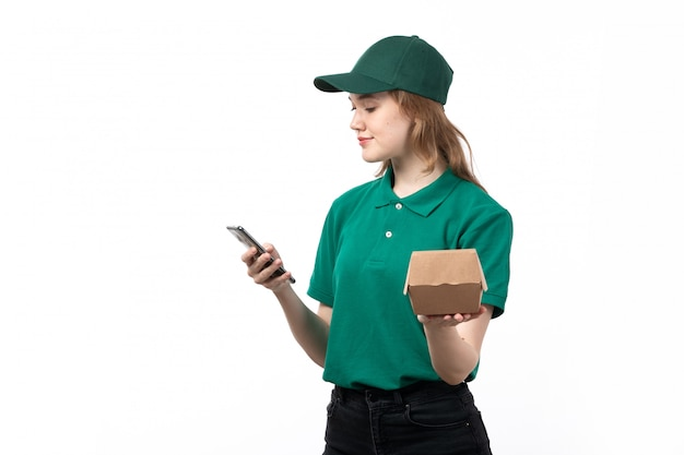 A front view young female courier in green uniform holding package with food and using a phone