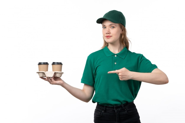 A front view young female courier in green uniform holding and pointing out coffee cups smiling on white