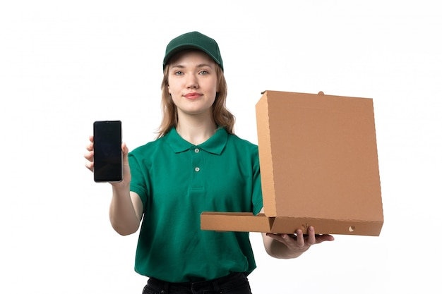 A front view young female courier in green uniform holding smartphone and open pizza box