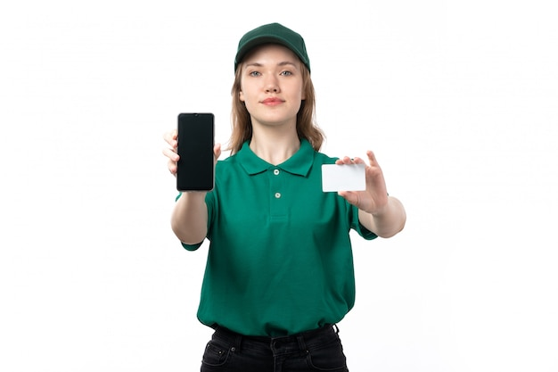 A front view young female courier in green uniform holding smartphone and white card smiling