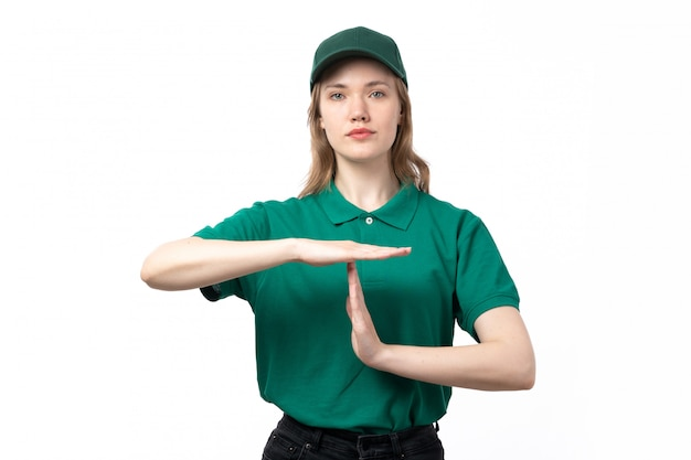 A front view young female courier in green uniform posing forming t letter