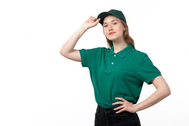 Un giovane corriere femminile di vista frontale in uniforme verde che posa toccando il suo berretto con il sorriso sul suo fronte