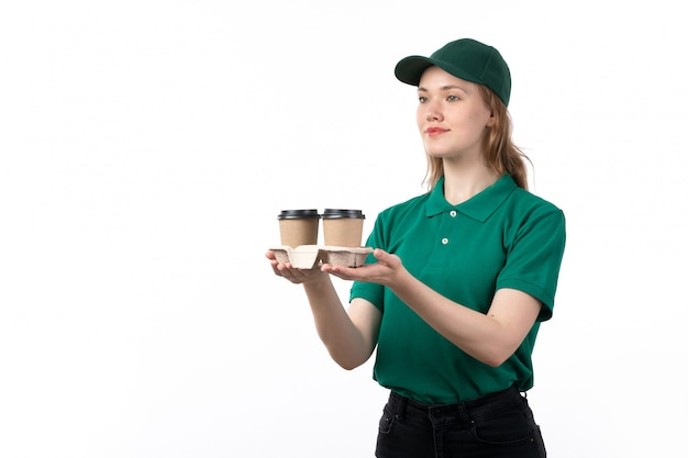 A front view young female courier in green uniform smiling delivering coffee cups