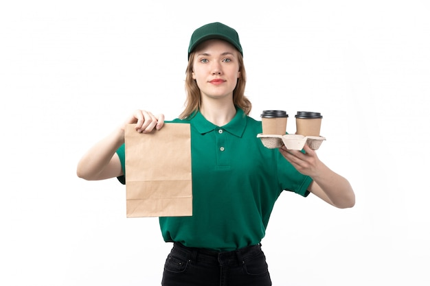 A front view young female courier in green uniform smiling holding food package and coffee cups