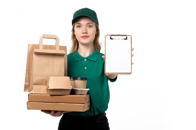 A front view young female courier in green uniform smiling holding food packages boxes and asking for the signature