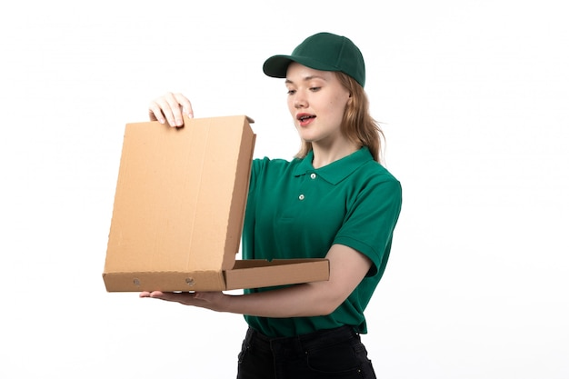 A front view young female courier in green uniform smiling holding package with food opening it empty
