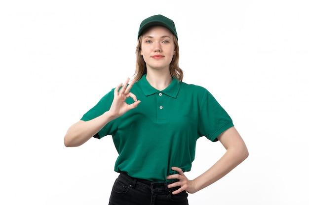 Un giovane corriere femminile di vista frontale in uniforme verde che sorride e che mostra bene il segno
